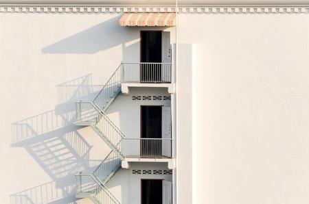 ordenanza: escalera de incendios con las sombras de la tarde en la pared blanca Exter.
