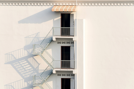 fire escape: fire escape with afternoon shadows on exterior white wall. Stock Photo