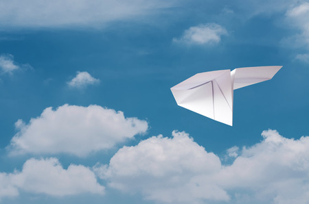clear away: Paper plane flying over clouds with blue sky.