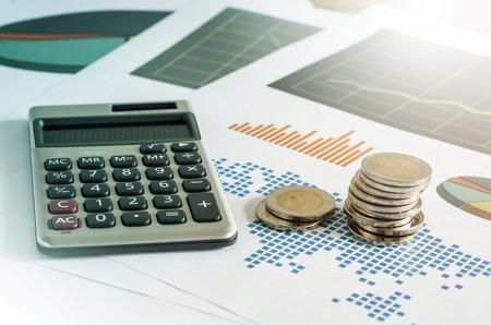 동전 스택과 금융 그래프의 종이에 계산기. 비즈니스 개념입니다. 컬러 필터.