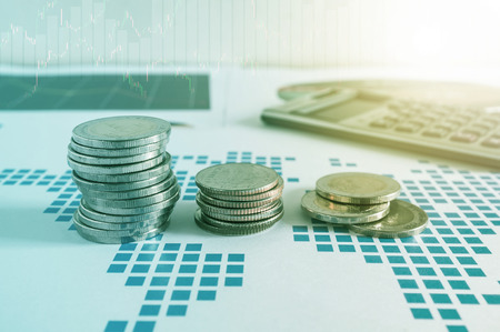 capital gains: Coin stacks and calculator on paper of financial graph. Graphics icons, worldwide stock exchanges. Business concept. Color filter.