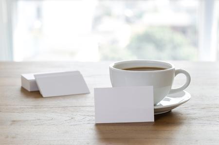 빈 명함 및 나무 테이블에 커피 한잔. 기업 고정 브랜딩 모의 업. 스톡 콘텐츠