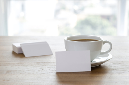 Blank business cards and cup of coffee on wooden table. Corporate stationary branding mock up.