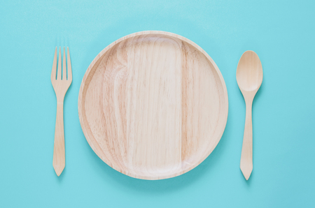 Dinner minimal background concept. Top view of empty wooden plate with fork and spoon on blue background. Flat lay.