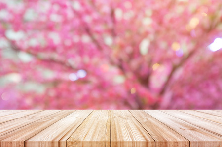 Empty wooden table top with blurred pink cherry or cherry blossom background. can be used product display.