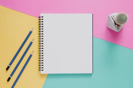 Office 직장 최소한의 개념입니다. 빈 노트북, 연필, 노란색, 분홍색 및 녹색 청록색 배경에 선인장. 복사 공간, 평면 누워와 상위 뷰. 파스텔 컬러 필터.