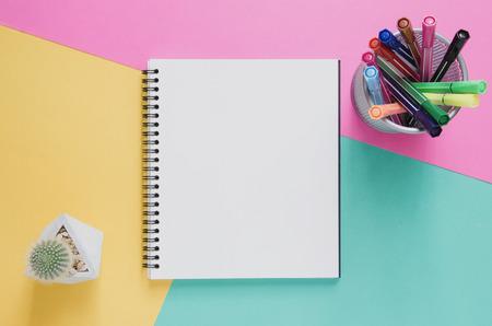 Kantoor werkplek minimaal concept. Leeg notitieboekje, de doos van de kleurenpen, cactus op gele, roze en groene turkooise achtergrond. Bovenaanzicht met platte kopie ruimte, lag. Pastelkleurfilter. Stockfoto - 82670912