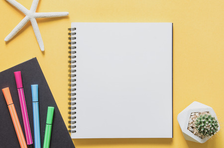 Office workplace minimal concept. Blank notebook with starfishes, cactus and color pen on yellow background. Top view with copy space, flat lay. Pastel color filter. 版權商用圖片