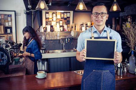 커피가 게에서 빈 칠판 메뉴를 들고 웃 고 아시아 바리의 초상화. 카페 레스토랑 서비스, 중소 기업 소유자, 음식과 음료 업계의 개념.