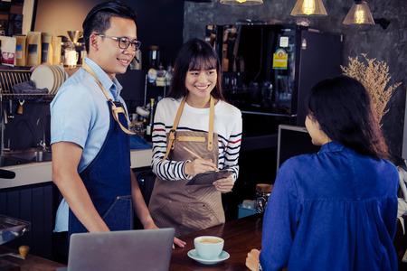 Dos de los baristas asiáticos que ordenan en la barra contraria en café. Servicio de restaurante de café, concepto de industria de alimentos y bebidas. Foto de archivo