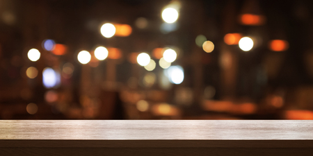 Empty wooden table top with blur coffee shop or restaurant interior background, Panoramic banner. Abstract background can be used for display or montage your products. 免版税图像