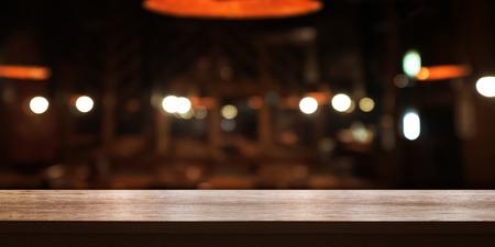 Piano d'appoggio di legno vuoto con la caffetteria della sfuocatura o il fondo interno del ristorante, insegna panoramica. Lo sfondo astratto può essere utilizzato per visualizzare o montare i tuoi prodotti.