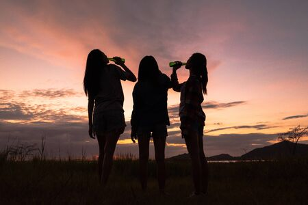 Group of young asian women cheering, drinking alcohol, having fun on weekend celebration with beautiful sunset. Friendship lifestyle and traveling concept.