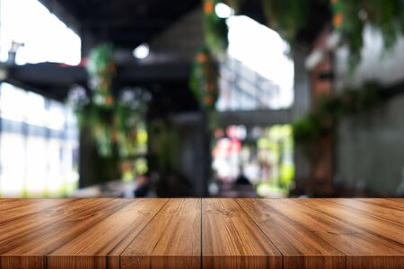 Empty wooden table top with blurred coffee shop or restaurant interior background. can be used product display.