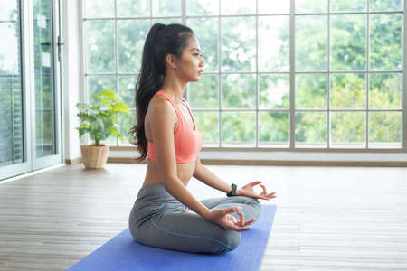 Training at home. Young asian woman doing yoga exercises with palms in Namaste, meditating, breathing and relaxing, while online tutorial on mobile phone.