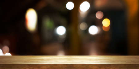 Empty wooden table top with blur coffee shop or restaurant interior background, Panoramic banner. Abstract background can be used for display or montage your products. 版權商用圖片