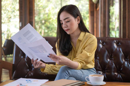 Young Asian businesswoman sitting in cafe and reading documents. Female working with financial documentation and financial reports before meeting.
