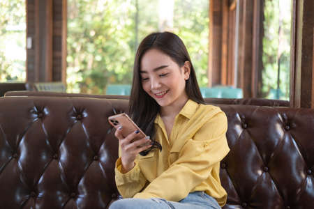 Smiling young Asian woman using smartphone at coffee shop. Asian female reading text message or social media on cell telephone during in modern cafe. Working online technology system concept.