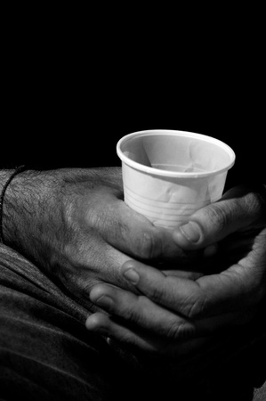 Beggar holding cup for coins photo
