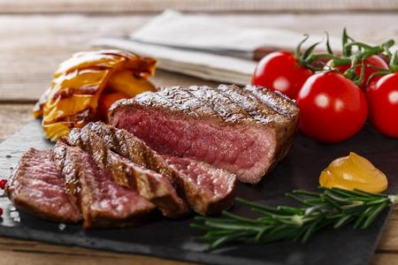 나무 표면에 야채와 구운 쇠고기 스테이크