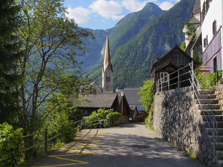 lakefront: View street Hallstatt village with church bell tower on lake shore and Alps behind, Austria