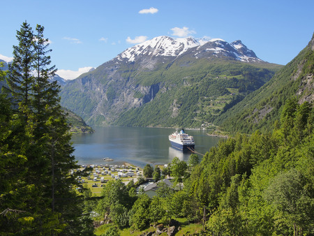 water scape: Geiranger fjord, Norway with cruise ship, mountains and village, summer, June 28, passenger ship, forest, trees