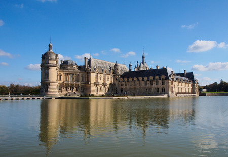 chantilly: Chantilly castle with reflection in the water, blue sky, clouds, day