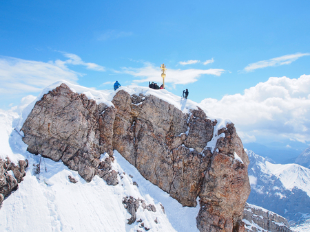 Gold cross stands at the summit of the Zugspitze, highest peak in Germany.