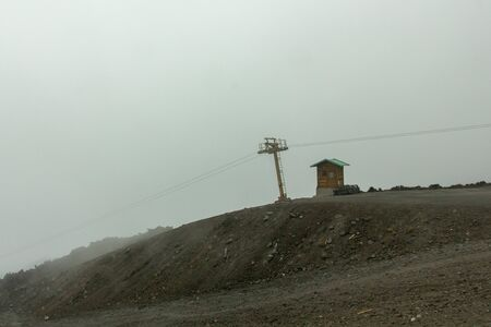 Landscape of Etna with cable car in the fog, Sicily, Italy Stock Photo