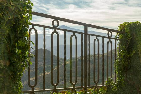 View of the Etna volcano in the clouds throw the garden grate from Castelmola Sicily