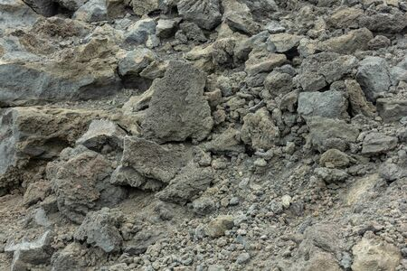 Background of stones on the black ground of Lava of a Etna Volcano
