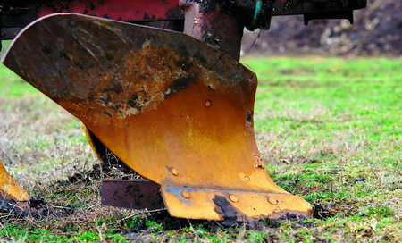 plow for plowing the land. Standing on the green grass of the field before preparing for the sowing process