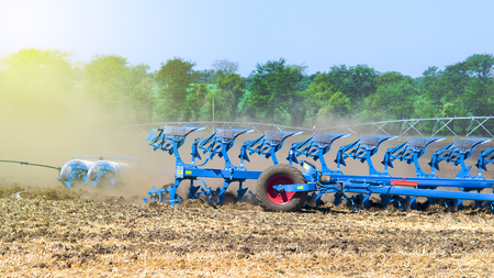 Tractor with a system of plows for the cultivation and plowing of the land against the background of the rising dust and glare of the sun. Stock Photo