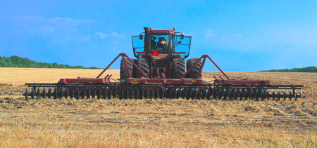 Red tractor for harvesting in the mid-summer season, produces disk field Imagens