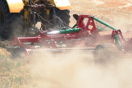 disc drive on the tractor while working on the field in dust clouds closeup