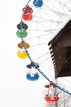 Ferris wheel under the snow. Bright colored booths without people. The snow stopped the wheel.