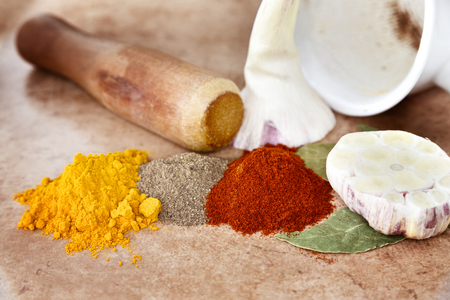 Mortar for spices, garlic and Bay leaf. Handful of paprika black pepper and turmeric. Stock Photo