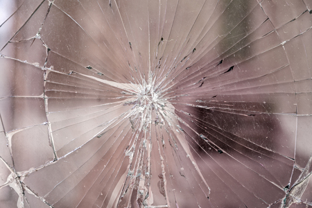 Texture of broken glass. Broken window glass. Chipped automotive glass. Cracks on the mirror.  For photomontage and collage. Stock Photo