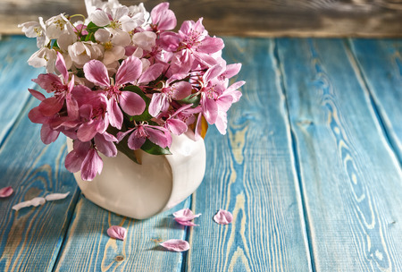 Sakura in vase. Red delicate Japanese flowers in a small vase standing on the table. Table of blue planed boards. Painted surface of the table. The blue color of the boards. Fallen flower petals. Stok Fotoğraf