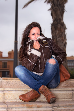 Frau sitzt auf Leiter Standard-Bild