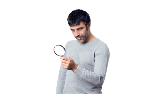 Dark-haired man looking with magnifying glass on white background Standard-Bild