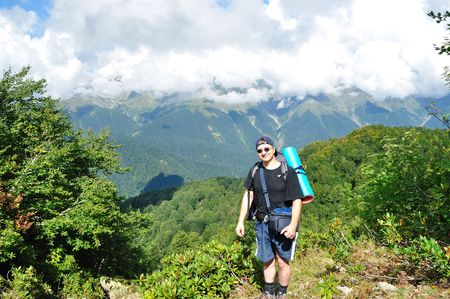 climbed: Tourist climbed to the pass, the background mountains, clouds, trees
