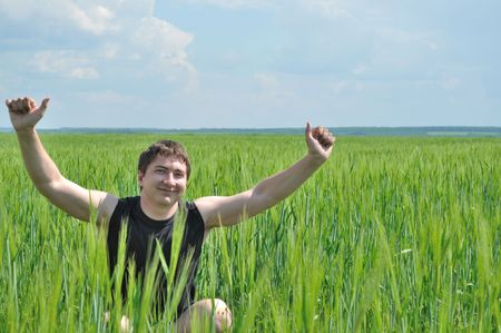 One man, sitting in a field of green wheat, smiles,raised his hands up photo