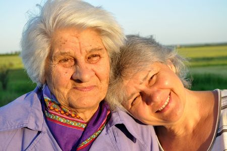 Two elderly women, one of which put her head on the other shoulder photo