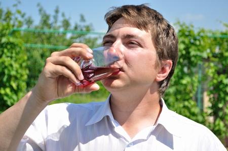 gladly: El hombre con mucho gusto beber jugo de cereza, con un vaso  Foto de archivo
