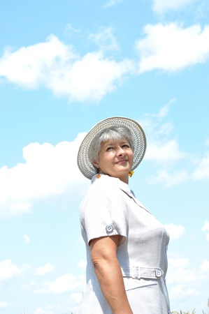 Middle-aged woman in a hat against the sky photo