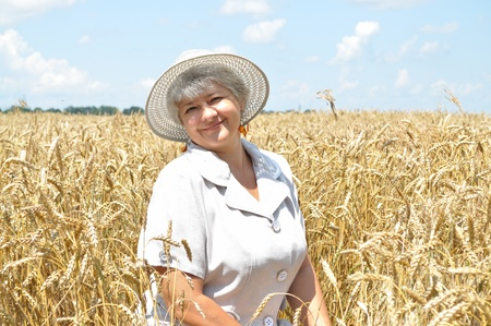 Middle-aged woman in a hat, amid fields of wheat photo