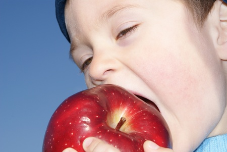 eagerly: The child eagerly bites big red apple, blue cap, background sky