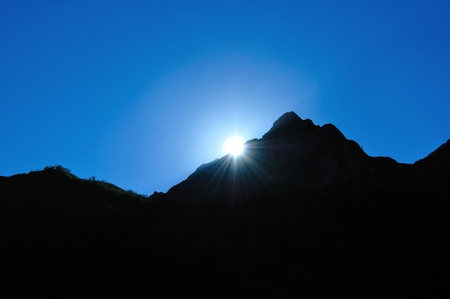 Bright sun at sunset, hiding behind the mountain, sparkling rays photo