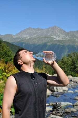 The young man eagerly drinking water from plastic bottles, white mountain river, mountain top photo